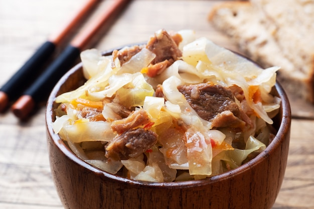 Stewed cabbage with meat in a wooden bowl on a wooden background. traditional russian dish of solyanka.