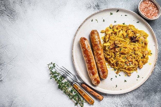 접시에 버섯과 고기 소시지와 양배추 조림