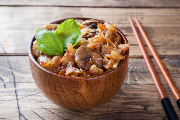 Stewed cabbage with mushrooms on the old wooden background in rustic style
