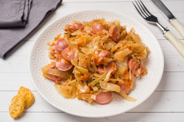 Stewed cabbage with sausages in a plate on the table.