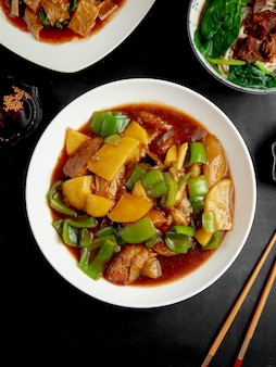 Stewed chicken with pumpkin and peppers on black table