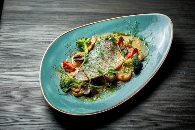 Тушеная дорадо с тушеными овощами и соусом песто на синей тарелке. блюдо из морепродуктов
