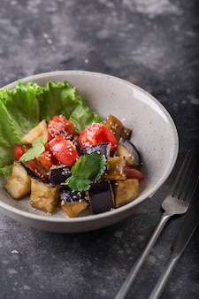 Stewed eggplant and tomato salad with lettuce and sesame seeds on a white plate.