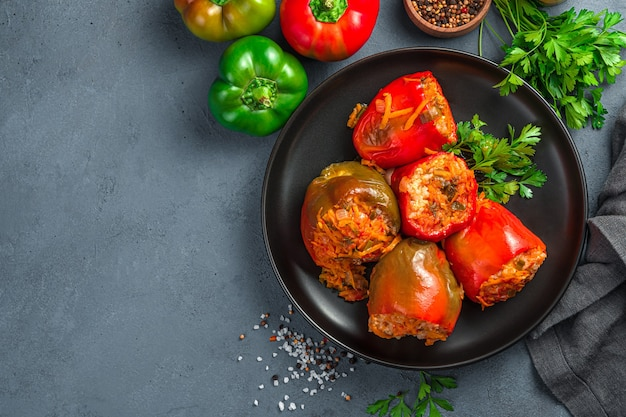 Stewed homemade stuffed bell peppers and fresh herbs on a dark grayblue background