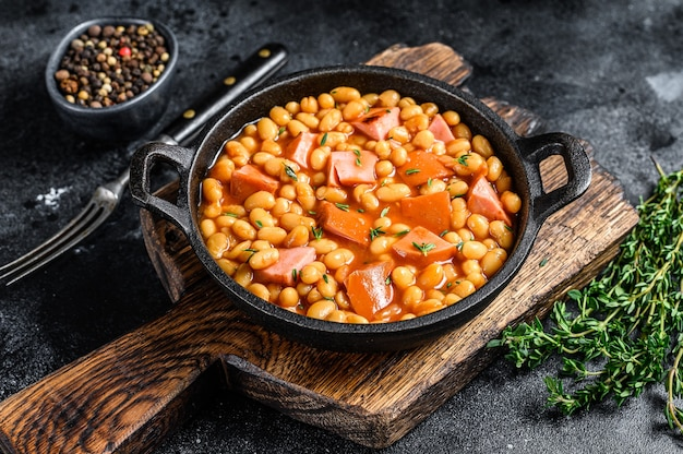 Stewed kidney beans with smoked sausage and tomato sauce in a pan. black background. top view. copy space.