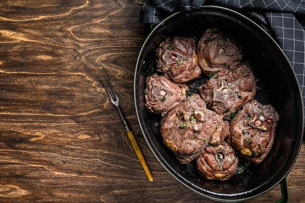 Тушеное мясо ягненка на сковороде с зеленью.
