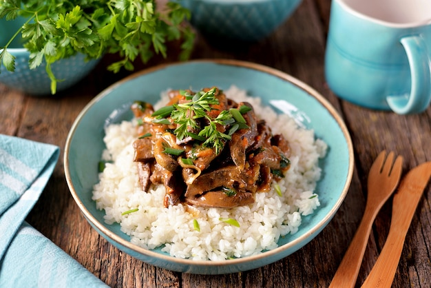 Stewed liver in a sauce with onion, carrot and parsley and boiled rice