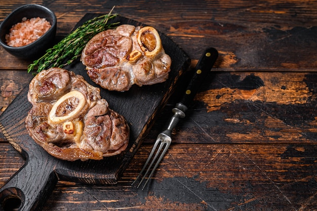 뼈에 스튜 고기 오쏘 부코 쇠고기 정강이, 이탈리안 오소부코 스테이크. 어두운 나무 배경입니다. 평면도. 공간을 복사합니다.