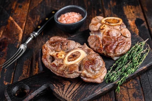 뼈에 고기 조림 osso buco 쇠고기 정강이, 이탈리아 ossobuco 스테이크. 어두운 나무 배경입니다. 평면도.
