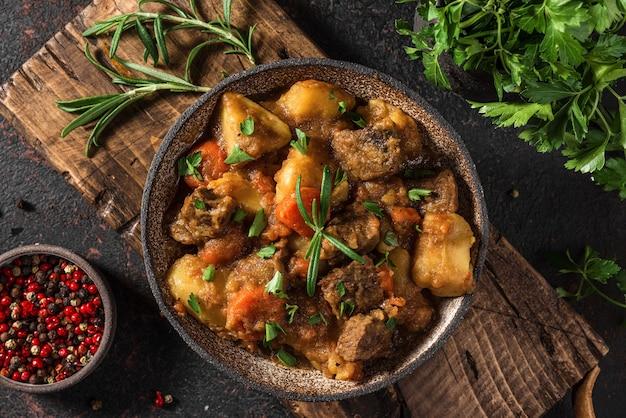 黒い表面のプレートにジャガイモ、ハーブ、ニンジンを添えた肉の煮込み
