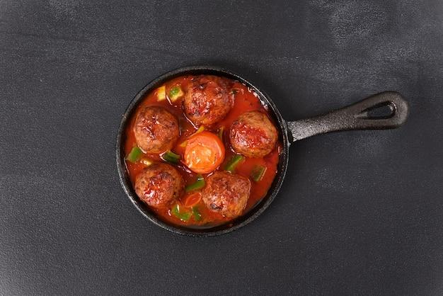 Тушеные тефтели в томатном соусе на сковороде на темном столе.