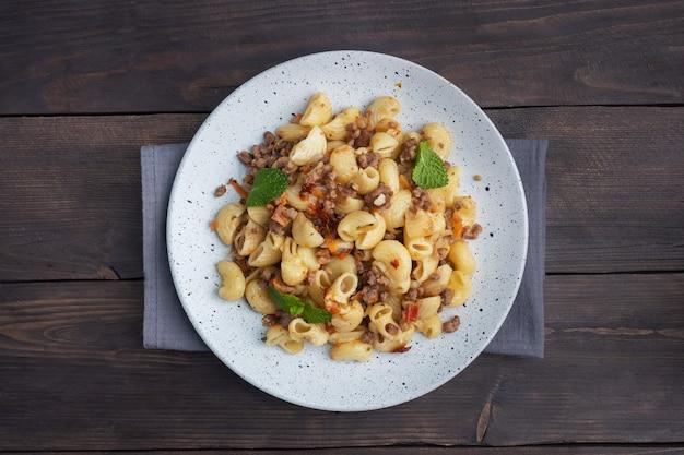 牛挽肉と野菜の煮込みパスタ、ネイビースタイルのマカロニをプレートに。暗い木の背景。スペースをコピーします。