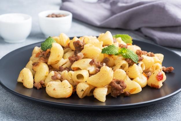 다진 쇠고기와 야채를 곁들인 조림 파스타, 접시에 네이비 스타일의 마카로니. 회색 콘크리트 배경입니다.