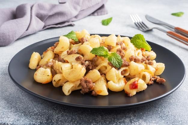 Тушеные макароны с говяжьим фаршем и овощами, макароны в стиле navy на тарелке. серый бетон