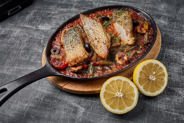 Stewed perch in tomato sauce, serve food in the provencal style, in a pan.