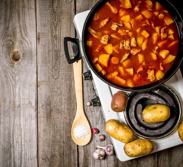 Тушеный картофель с мясом и специями в электрической плите на деревянном фоне