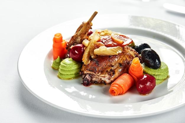 가벼운 접시에 메추라기 조림, 야채와 올리브, 밝은 배경, 스튜로 요리 한 메추라기, 케이터링 제공.