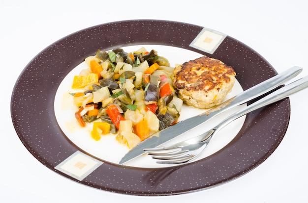 Stewed seasonal vegetables, homemade cutlet for dinner. studio photo.