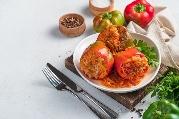 Stewed stuffed pepper with turkey rice and vegetables on a light background