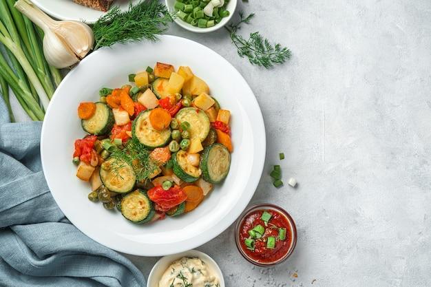 灰色の背景に白いプレートで煮込んだ野菜。健康的なベジタリアン料理。