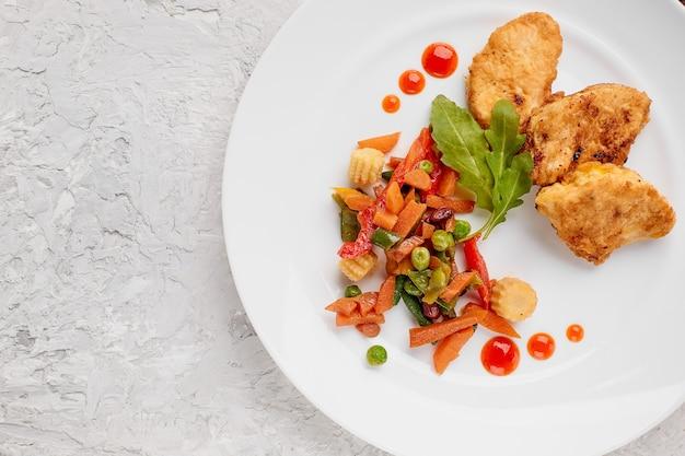 ハーブとチキンステーキを白いプレートにバッターで煮込んだ野菜と灰色のコンクリートの背景にケチャップの滴を載せたトップビューフードメニューとテキストをコピーする場所