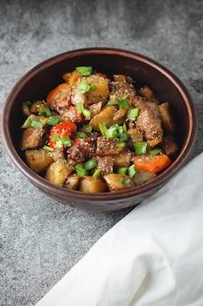Тушеные овощи со специями в глиняной посуде на темно-сером грифельном или каменном фоне.