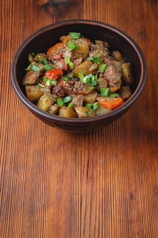 Тушеные овощи со специями в глиняной миске на темном деревянном фоне.