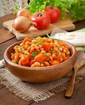 Тушеная белая фасоль и нарезанная тыква в томатном соусе