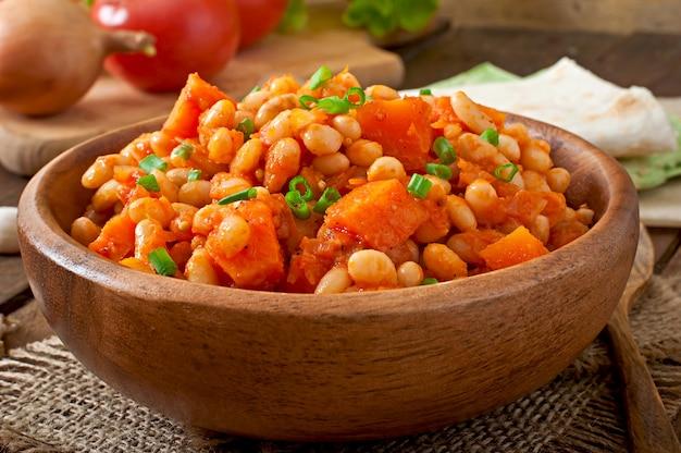 白豆の煮込みとスライスしたカボチャのトマトソース