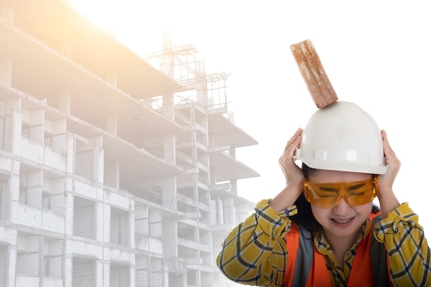The stick block brick fell on the asia engineer young woman head on the helmet worker