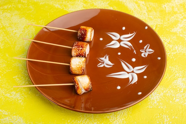 Палка конфитюр внутри коричневой тарелки на желтом фоне закуска фото цвет еда еда
