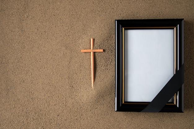 砂の上に額縁と十字架を貼り付けます