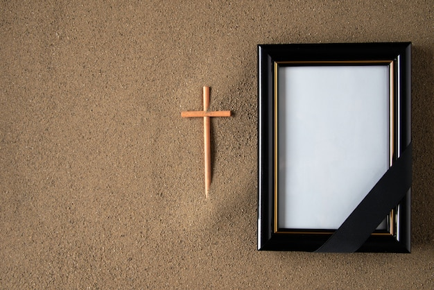 Stick cross with picture frame on the sand