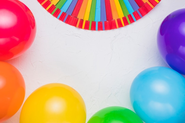 Stick rainbow and colorful balloons on white surface