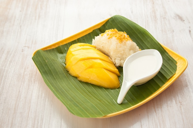 Stick rice with mango on the banana leaf and yellow plate thailand dessert