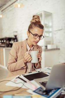 仕事に固執する。両手で一杯のコーヒーを保持し、彼女のラップトップを見ている集中した美しい女性。