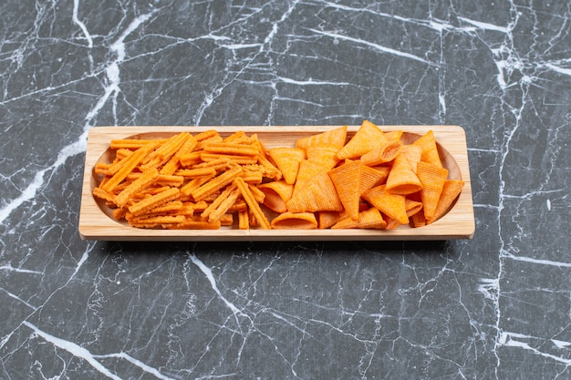 Stick e patatine triangolari sul piatto di legno.