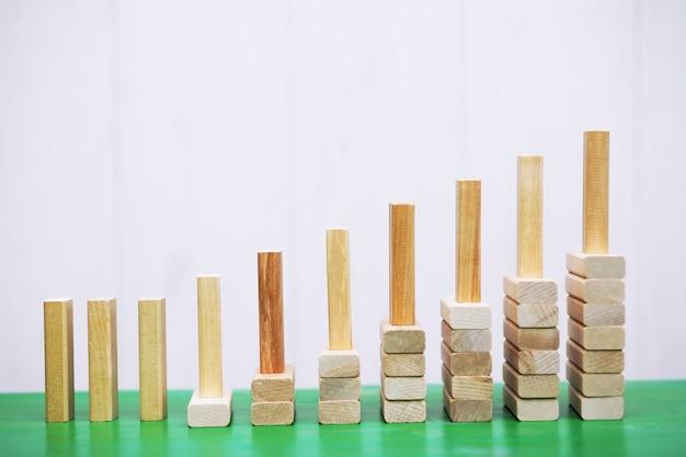 積み重ねられた正方形のウッドブロックの上に立っているスティックウッドブロック、勝利、成功、挑戦、トップポジションへのステップの概念の抽象的な背景。