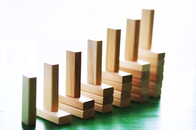 Stick wood block standing on stacked square wood blocks, abstract background in concept of winning, success, challenge, step to top position.