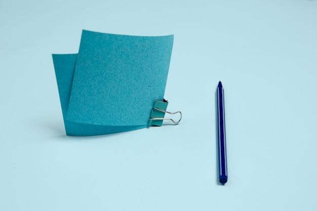 ステッカー用紙、ペン。スタジオの壁に青い色のモノクロのスタイリッシュでトレンディな構成。