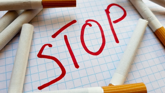 A sticker that says stop is in a pack of cigarettes. world no tobacco day. quit smoking. fight with cigarettes.