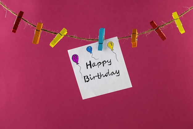 Sticker with the inscription on paper happy birthday on a rope with clothespins