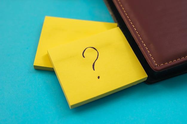 노란색 정사각형 모양의 스티커가 파란색 벽에 붙습니다. 메모 및 미리 알림을위한 메모장. 잎사귀에 물음표가 적혀 있습니다.