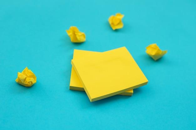 노란색 정사각형 모양의 스티커가 파란색 벽에 붙습니다. 메모 및 미리 알림을위한 메모장 텍스트를위한 빈 공간.