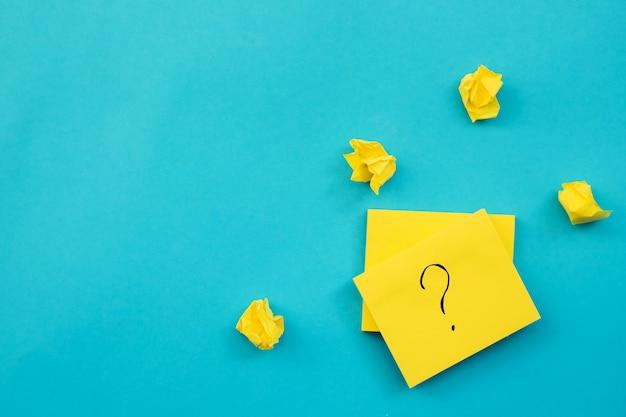 노란색 정사각형 모양의 스티커가 파란색 벽에 붙습니다. 메모 및 알림을위한 메모장 주변에 구겨진 종이 덩어리가 있습니다. 잎사귀에 물음표가 적혀 있습니다.