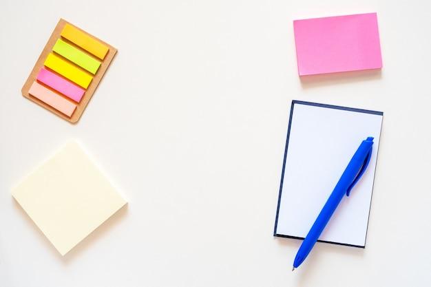 밝은 흰색 배경에 스티커 메모장과 펜 색 사무용품 프레임 플랫 누워