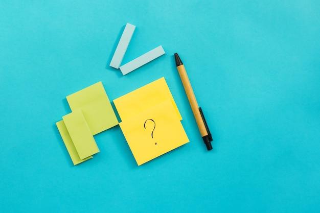 青い壁にはさまざまなサイズや色のステッカーが貼られています。その隣にペンがあります。メモやリマインダー用のメモ帳。葉にはクエスチョンマークが書かれています。