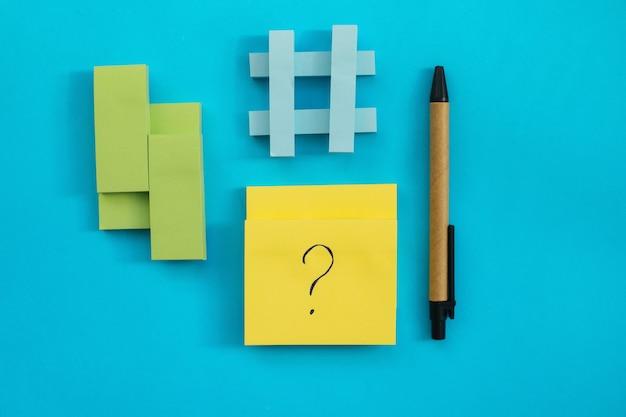 Наклейки разных размеров и цветов размещаются на синей стене. рядом есть ручка. блокноты для заметок и напоминаний. на листе написан вопросительный знак.