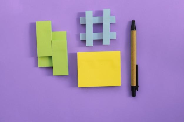На розовую стену помещены наклейки разных размеров и цветов. рядом есть ручка. блокноты для заметок и напоминаний. плоская линия.