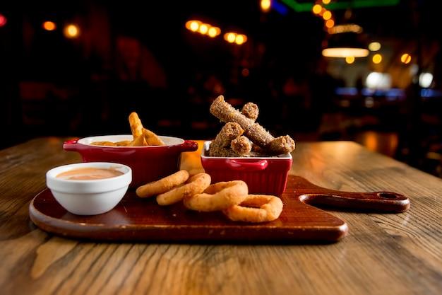 Палочки, жареный лук и жареные помидоры с соусом